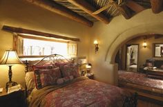 Bedroom of an earth bag home: looks cozy and appealing. Check out the ceiling!