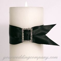 Pillar candle decorated with black satin ribbon & a rectangular rhinestone buckle.