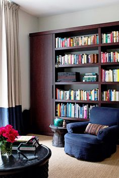 Cozy reading nook with chocolate brown shelves, floor to ceiling curtains and a blue armchair