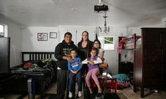 Victor, 29, and Nicole, 26, pose with their children: Victor, four; Sherlin, nine; and Jasmine, eight, in the car garage where they have lived for the past three years, in Menlo Park, California.