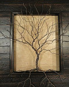 This beautifully crafted wire tree sits inside a distressed, dark brown stained, salvaged wood look photo frame. Its branches and roots reach up, out and over the frame, grabbing into nooks and crannies in the frame to hold itself in place, making this tree have a unique 3-D