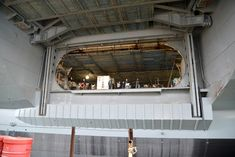 A glimpse into the hangar deck through the port elevator, which is in the raised position. Note the extensive staging below the hangar overhead (ceiling) to allow work to continue.