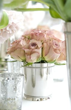 antique roses in silver julep vase...a little more formal, but lovely. I have these silver vases.