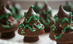 Little trees made from Hershey's Kisses atop stacked king-size and miniature Hershey's Peanut Butter Cups, decorated with green icing and round sprinkles