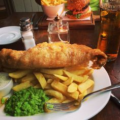 Authentic fish, chips, mushy peas, and cider at Prince Bonaparte in London, UK.