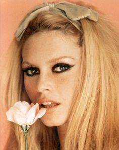 brigitte bardot. I ADORE this hairstyle and makeup look. Dramatic dark lined cat eyes, nude lip and a bow on the crown of your head <3