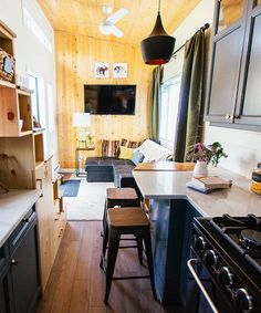 The galley kitchen features a four burner gas stove, a deep single bowl sink, an apartment size refrigerator, upper cabinets, and a full height pantry.