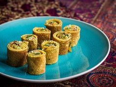 Mini Masala Dosas with sprinkleof coriander, on bright blue plate and red patterned carpet background
