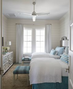 This gray and blue beach style shared bedroom features two carved gray headboards on twin beds dressed in white and blue bedding. A pair of blue benches sit at the foot of two beds facing a gray quatrefoil mirrored cabinet tucked under a flat panel tv.
