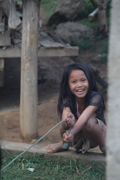 Smiling sitting girl playing rope - Bokeo, Laos