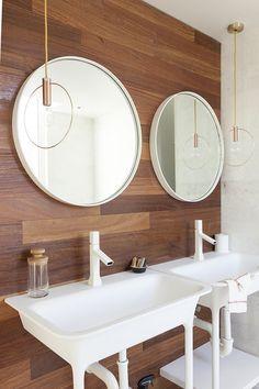 Brass lighting fixtures mimic large circular mirrors hanging over free standing vanities.