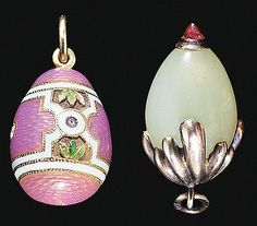 Two antique Fabergé egg pendants, one in pink guilloche enamel with matte white enamel bands, green enamel leaves and diamonds, one of bowenite with a cabochon ruby tip and mount of gold leaves.