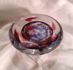 This one of a kind, shallow paperweight bowl was hand blown by a glass artist in Washington. The solid glass bowl was molded by hand and features