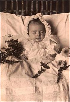 (foto post-mortem de un bebe de apenas unos meses, el niño se ve muy risueño pero la flores a su alrededor evidencian que ha pasado a mejor vida)