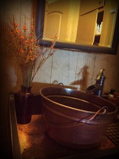 Copper bucket sink and brushed pump faucet sits atop a dry sink I redid in my primitive bathroom. By ye olde crow primitives.