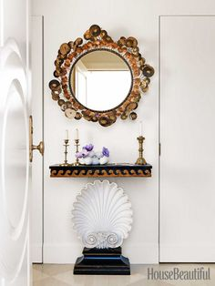In the foyer, a Raindrops mirror by C. Jere hangs over a vintage Edward Wormley shell console table.