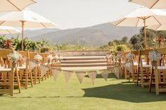 The ceremony site, roped off with a welcome sign stenciled on burlap; baby's breath aisle-markers coordinate with the off-white umbrellas, thoughtfully provided to shade the guests.