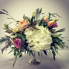 White hydrangea, peach garden roses, tulips, pink lisianthus, dusty miller, free form centerpiece