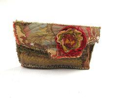 This earthy upcycled clutch bag is made with upholstery scraps that I have collaged together to come up with an artistically designed, one of a kind clutch purse, reminiscent of the carpet bag.    Ive used colors of my favorite season - autumn.   There is plenty of room in this bag to carry all of your essentials.  12 x 6.5    Ive accented it with a rose that was formed out of trim off of a former occupant of my closet.    It will have a magnetic snap closure.  Hand and machine sewn…