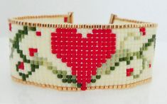 This beautiful handmade heart and vines wrap/cuff bracelet design has been created using a bead loom using size 11 miyuki delica seed beads in gold, red, cream, and various shades of green. Beads are hand woven using a durable c-lon nylon thread and finished with a gold filled