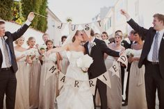 "love the whole bridal party being in the shot with the ""just married"" bunting!"