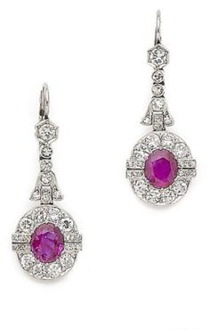 A pair of art deco ruby and diamond pendent earrings, first half of the 20th century Each oval-cut ruby, within a brilliant and single-cut diamond surround, suspended from an articulated row of similarly-cut diamonds with fleur-de-lys detail, millegrain-set throughout.
