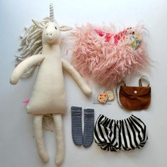 This lovely, unique unicorn doll has a sense of style all her own (of course, she is a unicorn, after all...)--she comes with a shaggy pink fur wrap (lined with a colorful print designer fabric by Anna Maria Horner), a pair of striped black and white bubble style pantaloons, and tall black and white stripey stockings. She also has a faux suede back pack that opens and closes with a button in which she has stashed the favorite lunch of unicorns--a sprinkle and sparkle sandwich. The unicorn is…