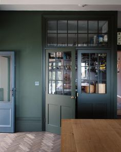 Dark green kitchen with built-in pantry by Plain English.