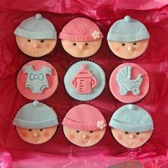 Nine baby shower cupcakes, decorated with pink and blue icing and baby faces