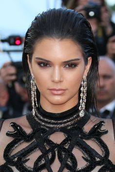 Kendall Jenner with mocha eyes, nude lips, bold brows, slicked back hair with statement earrings