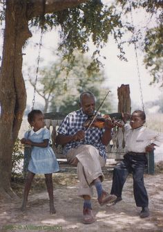 """Butch Cage entertaining neighborhood children with his violin in Zachary, Louisiana, summer 1960; source: William Claxton & Joachim E. Berendt """"Jazzlife - A Journey for Jazz across America in 1960"""".- Köln/Cologne (Taschen) 2013, p. 60; photographer: William Claxton"""