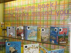 Back to School bulletin board featuring book jackets with eyes.  Welcome back!  The books missed you.  Used book jackets with large eyes glued on, glued to file folder for support. Wrapping paper background (from dollar store).