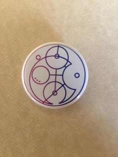 This 1-1/4 inch button features the word bisexual written in circular Gallifreyan, in the colors of the bisexual pride flag.