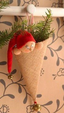 Cute Christmas elf peeking from a burlap cone.