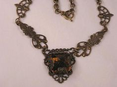 A Victorian design that simply required assembling the right parts with jumps.  The focal is a large old Czech stone set up side down, encased in a manipulated filigree (some call them turtles) and glued to the backing filigree.  A small metal plate was then glued to the back of the focal for signature as well as to hide any stray glue.