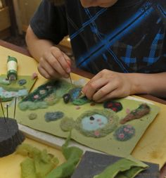 This is my 7 yr. old grandson working on his own play mat for gnomes and legos. He is using a needle felting needle and working on a foam cushion, mostly using scraps of wool roving.