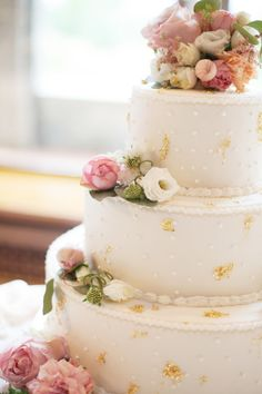 Dots, gold leaf and rustic floral details on this wedding cake...