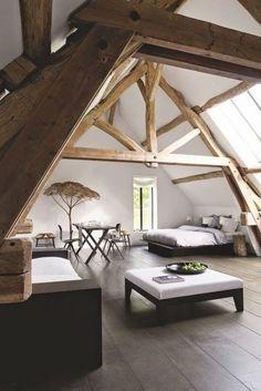 Prachtige leefruimte op zolder, met bed, tafel en zithoek. De oude houten balken zorgen voor een fantastische sfeer, in combinatie met de moderne inrichting.