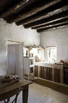 white stucco kitchen w/ wood beams and glowing window