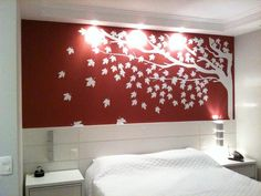Stunning bedroom desig with tree wall decal in red painting wall as well white bedding including wall lamp over the vanity