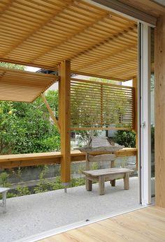 借景を生かす 西日対策:蔀戸、 敷地の西側は、水路を隔てて隣家の緑が広がっている。それを借景として取り込んだ。問題は西日対策である。西側にサンルームを設け、木製ルーバーによる蔀戸(シトミド)を設置した。ルーバーの角度が変えられる簡単な仕掛けである。日差しを遮りながら風も視界も抜けることができる。