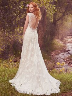 Maggie Sottero - TABRETT, This shimmering sheath features a layer of delicate lace appliqués over a layer of allover lace. Lace appliqués adorn the illusion cap-sleeves, illusion sweetheart neckline, and illusion back with keyhole opening. Finished with covered buttons over zipper closure.