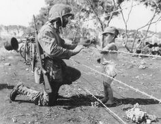 A Marine gives some food to a Japanese child on Saipan, 1944.