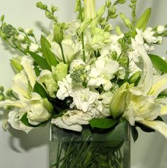 This is a cube vase floral arrangement that features casablanca lilies and dendrobium orchids in a white and cream color scheme.  See our entire selection at www.starflor.com.  To purchase any of our floral selections, as gifts or décor, please call us at 800.520.8999 or visit our e-commerce portal at www.Starbrightnyc.com. This composition of flowers is generally available for same day delivery in New York City (NYC). SQ025