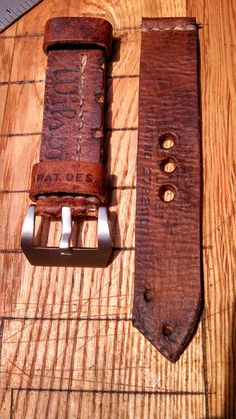 This is watch strap #008. Made of vintage Wilson baseball glove leather Hole side of the strap measures 145mm and is 24mm wide with natural cut edges and pointed end that follows the natural shape of the glove parts it was made with. Hole side has stamps from the when the glove was made. Buckle side is 88mm and has Wilson stamped on main bod of the strap. One keeper has PAT DES. 20708 This strap smells wonderful and is full of character, as only this vintage leather can have. Strap is a…