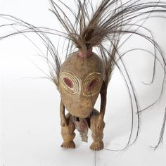 """Papua New Guinea; Namu Tribe carved hardwood Garra figure with large painted red eyes and cassowary feathers and leather ornamentation. H 6 1/4"""" x W 2 3/4"""" without feathers. Chip to one heel."""
