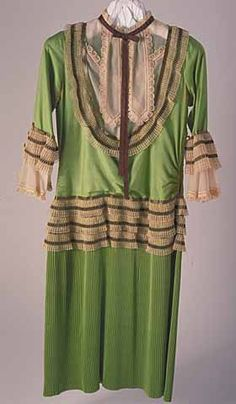 c1925-29 Chemise dress in chartreuse (green) silk has three-quarter length set-in sleeves ending in ivory chiffon engageantes trimmed with lace petal shapes. Lace also forms scallop at neckline collar lappets. Accordion pleated skirt has three tiers of cartridge pleated lace and bands of metallic gold ribbon at hip, yoke, neckline, and sleeves. Side seams are shirred. Brown grosgrain ribbon tie at neck. Side hook and eye closure at waist.