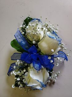 White roses tipped blue, baby's breath, silver beads, and green leaves on a wristlet with a blue bow. Blue Bow, Blue And White, Brownwood Tx, Wrist Corsage, Local Florist, Baby's Breath, Corsages, Boutonnieres, Flower Delivery