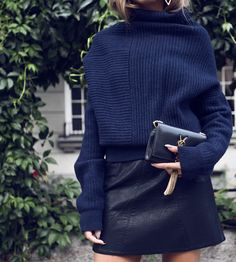 A navy turtleneck sweater paired with a leather mini skirt. This is the perfect outfit for a warmer fall day.