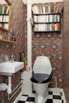 Lots of books in the half bathroom, and with william morris wallpaper to boot. 17 Ways to Squeeze in a Few Extra Books William Morris Wallpaper, Morris Wallpapers, Wc Retro, Wc Decoration, Decoracion Low Cost, Deco Cool, Staircase Landing, Sweet Home, Downstairs Toilet